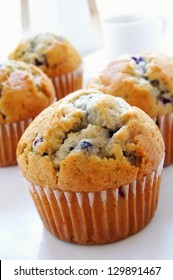 blueberry muffins with coffee cup and maker