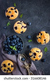 Blueberry muffins and fresh berries on dark background, top view