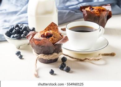 Blueberry muffins and fresh fruit, a cup of black coffee. Tasty dessert. Light breakfast. St. Valentine's Day. Dark background