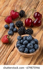 Blueberry and other berries assorted on a wooden table background, side view, big size resolution food photo