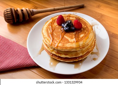 blueberry pancakes with honey, bamboo background, and utensils - hotcakes
