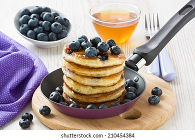 Blueberry pancakes with honey, maple syrup and berries