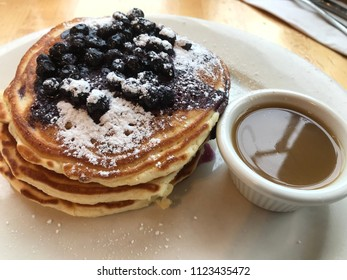 Blueberry pancakes topped with fresh wild blueberries and powdered sugar on white plate next to a white ramekin of maple butter syrup as seen from above.