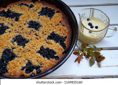 Blueberry pie and custard on a white wooden table with blueberry leaves for decoration