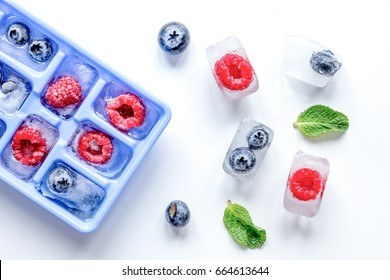 blueberry and raspberry in icetray on stone background top view