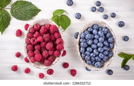 Blueberry and raspberry on white table top view