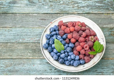 Blueberry and raspberry in plate on rustic table top view with copy space