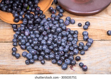 blueberry or raspberry scattered from pot over wooden background. Health and diet concept. Copy space.