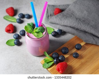 Blueberry and raspberry smoothie, pink berries milkshake in a glass with two drinking straw and mint leaves on rustic grey background.