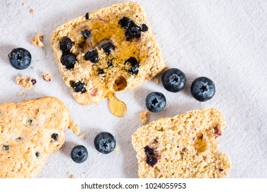 Blueberry scones on a white canvas background with a small pot of honey.