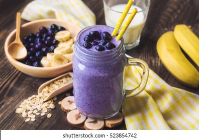 Blueberry smoothie with banana and oat flakes in jar on rustic wooden background.