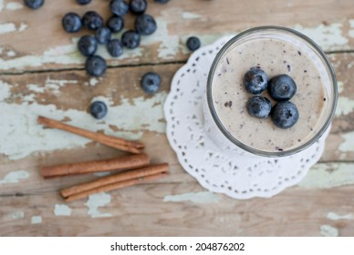 Blueberry smoothie with cinnamon sticks, delicious summer food on a rusty wooden table