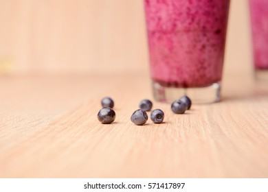 Blueberry smoothie with fresh berries, chia seeds and banana for breakfast on rustic wooden background, selective focus