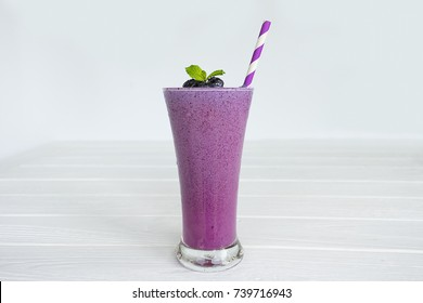 Blueberry smoothies purple colorful fruit juice milkshake blend beverage healthy high protein the taste yummy In glass,drink episode morning on white wood background.