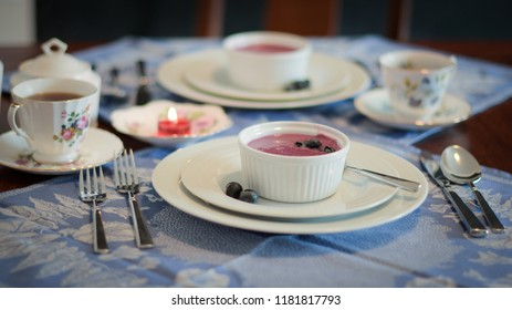 Blueberry Soup on blue place mats with a red candle and coffee.