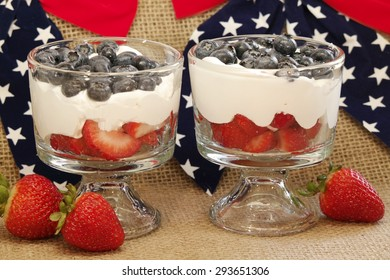 Blueberry and Strawberry Dessert Two dessert glasses filled with fresh strawberries, blueberries and cream.  The background is red, white and blue with stars and burlap.
