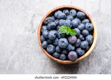 blueberry with vanilla mint in a wooden bowl on stone background ,top view