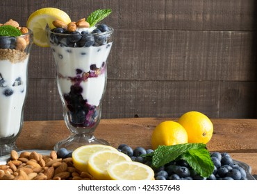 Blueberry Yogurt Parfait - healthy breakfast and snacks - ingredients in the front include almonds, lemon, fresh blueberries and mint