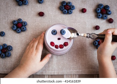 Blueberry yogurt with a smiling face. Child hands with yogurt. Top view