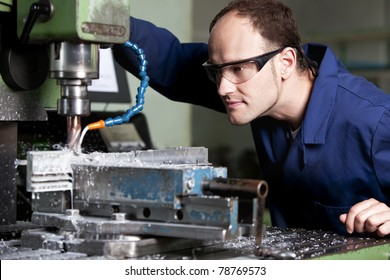 Blue-collar worker with safety glasses at milling machine in workshop.