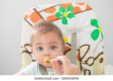 Blue-eyed baby boy eating in the baby's chair