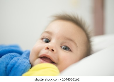 Blue-eyed baby boy lying on the bed