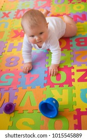 Blue-eyed baby learning to crawl with cups on bright alphabet mat.