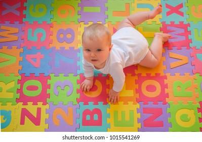 Blue-eyed baby playing on tummy on alphabet mats.