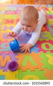 Blue-eyed baby reaching for cups during tummy time on foam alphabet mats.