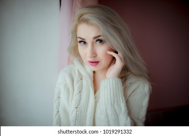 blue-eyed blonde in a white blouse near the window