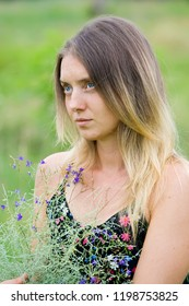 Blue-eyed blonde woman with a bouquet of sagebrush looks away