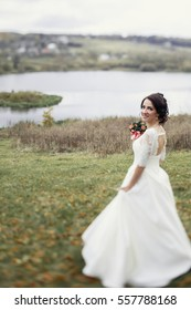 Blue-eyed bride holds pink wedding bouquet behind her face while she poses before the lake