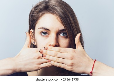 blue-eyed brunette girl covers her mouth with her hands