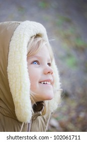 Blue-eyed girl smiling and looking up. Fall and cold, so a child wearing a hood