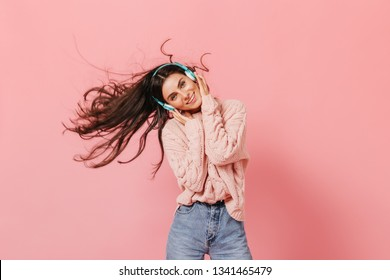 Blue-eyed girl with snow-white smile is listening to song in turquoise-colored headphones. Woman in knitted pullover dancing on pink background