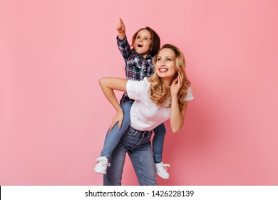 Blue-eyed lady sincerely laughs while playing with her little daughter. Portrait of adult and little girls in casual clothes on pink background
