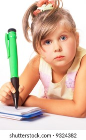 blue-eyed little girl with big green pen isolated on white