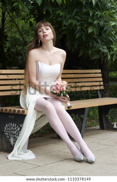 Blue-eyed, long-haired beautiful bride with bouquet of roses is sitting on the bench in the park