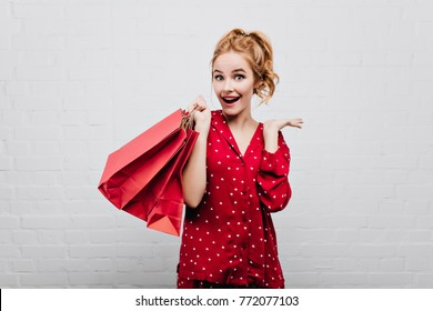 Blue-eyed surprised girl in cotton red sleepwear posing with smile on white background. Wonderful lady in pajamas having fun in birthday morning, holding gift bag.