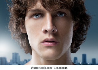 Blue-eyed young man in front of the outline of a big city.