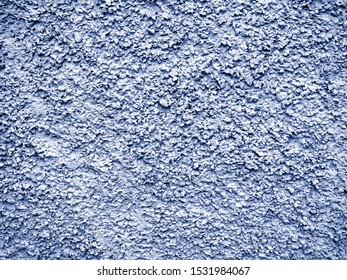 Blue-gray stucco with a chaotic convex pattern. The stone wall is covered with new rough plaster. Blue stucco background