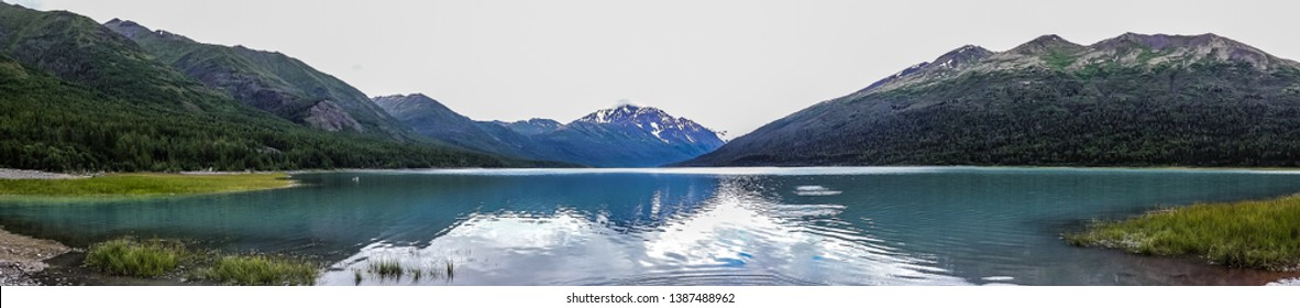 Bluegreen moutains reflected in the still water on a cloudy day at Eklutna Lake, Alaska.