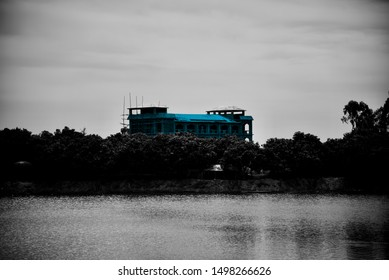 A blueish concrete building beside a lake unique photo
