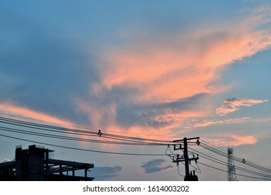 Blue-orange cloudy evening sky with electricity cable wires and contruction building and telephone network tower