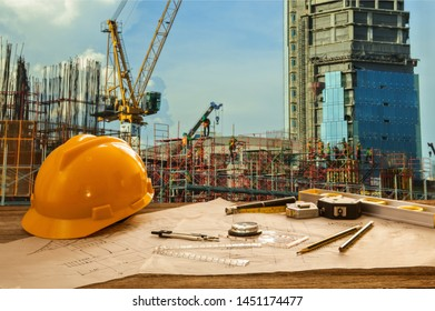 Blueprint and tool on table with building