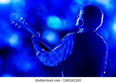 blues guitarist palying live on stage under blue light