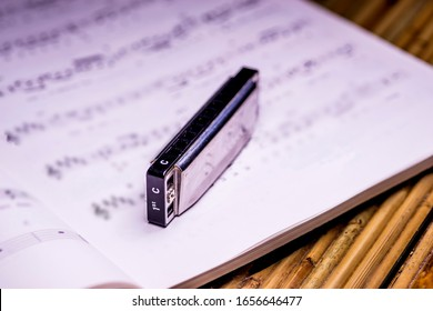 blues harmonica with notes in a closeup