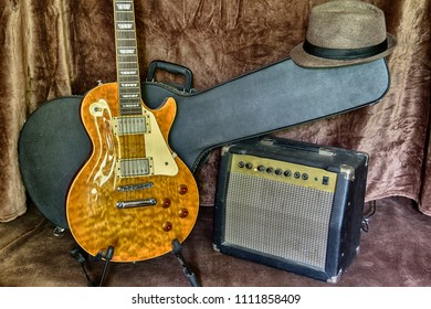Blues or rock musical instruments still life: electric guitar, case, combo amplifier and hat. Rock, metal or blues kit