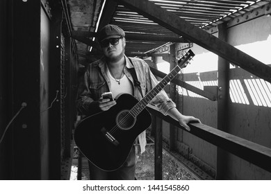 Bluesman with acoustic guitar in grayscale. Cool guy looks into smartphone. Wandering blues musician. Brutal bearded man travels light. Wandering hippie lifestyle. Eccentric man in monochrome.