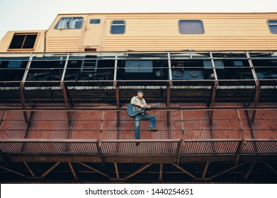Bluesman with acoustic guitar on railroad bridge. Cool guy plays guitar near running train. Showy performance of blues musician. Bearded man travels light. Wandering hippie lifestyle. Eccentric man.